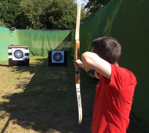 teenager pulls back the archery bow